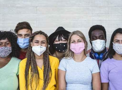 Sete jovens estudantes de máscara sorrindo para a câmera com os olhos.