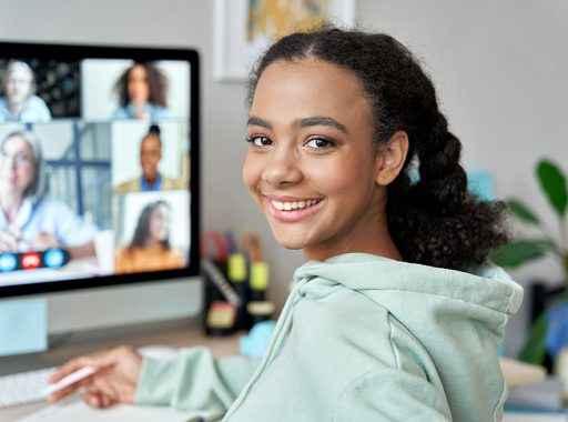Uma estudante secundarista sorrindo enquanto assiste aula online.