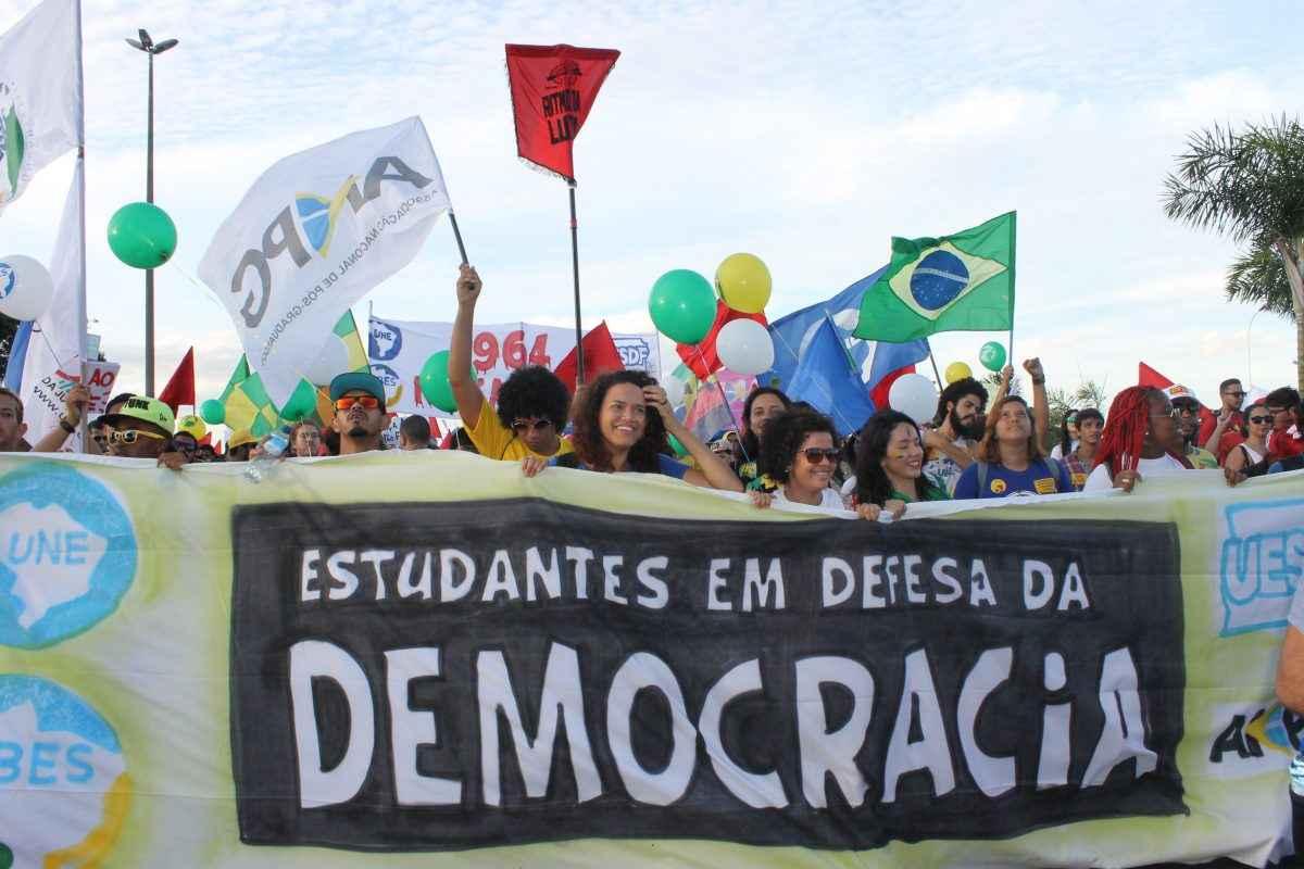 Passeata com faixa escrito Em Defesa da democracia