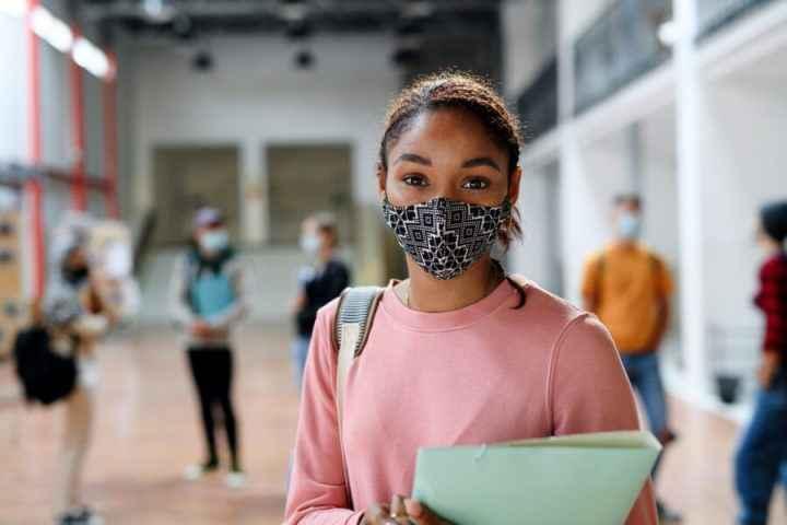 Uma menina estudante de máscara e blusa rosa de mangas compridas, segurando uma apostila, na escola.